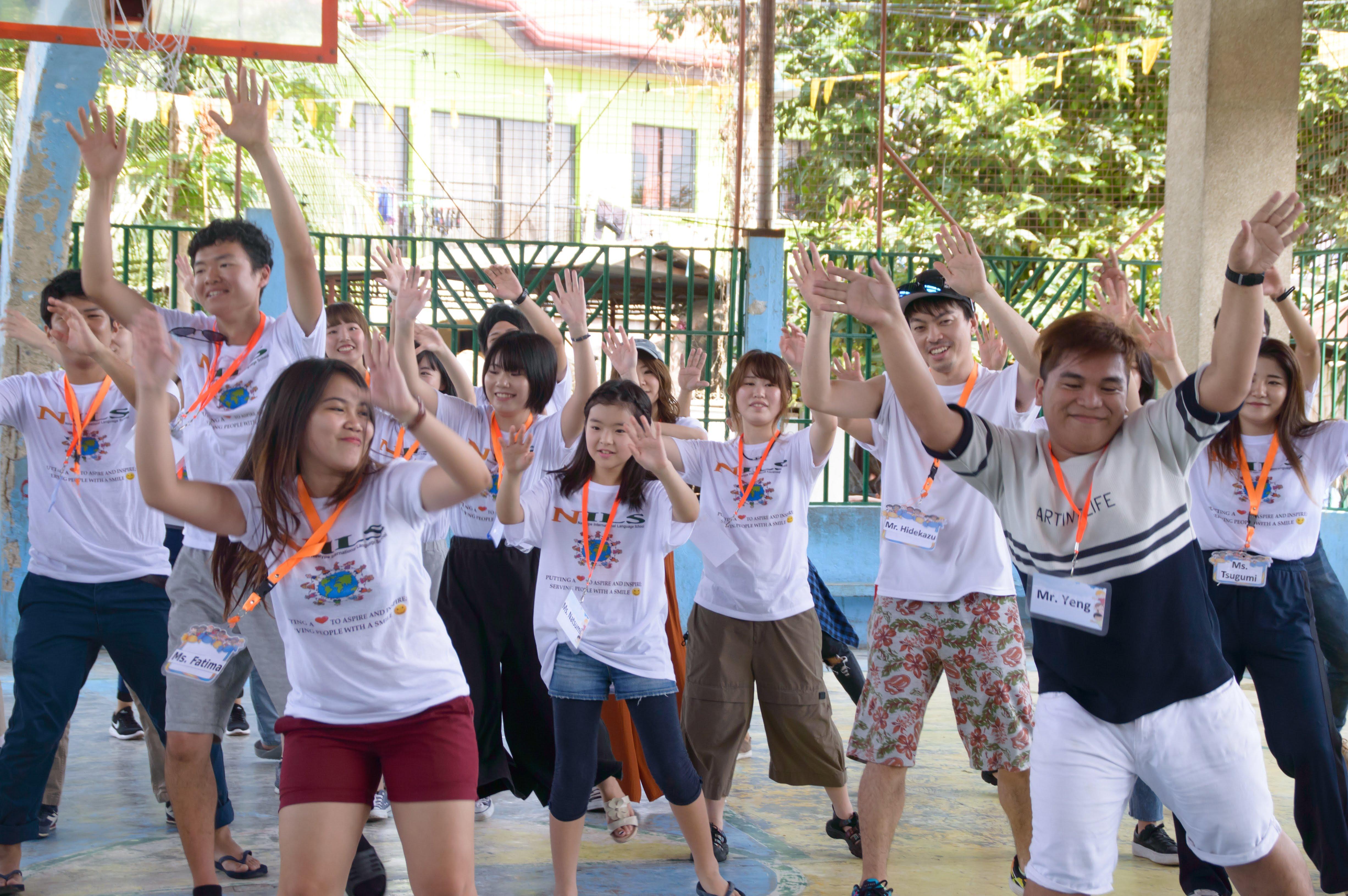子どもたちの前で留学生と先生がダンス