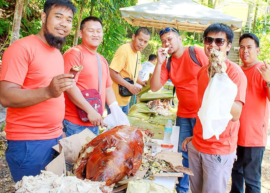 レチョン(豚の丸焼き)を食べるJICCスタッフたち